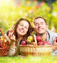 Happy People Eating Organic Apples in Autumn Garden.Healthy Food