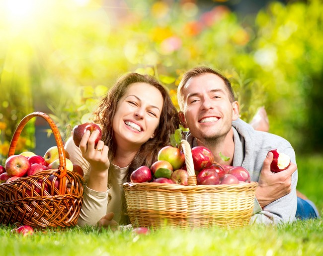Happy People Eating Organic Apples in Autumn Garden.Healthy Food