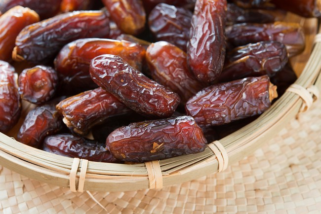 Dates fruit. Pile of fresh dried date fruits in a basket.