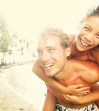 Happy young joyful couple having beach fun piggybacking laughing