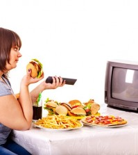 Big woman eating fast food and watching TV. Isolated.