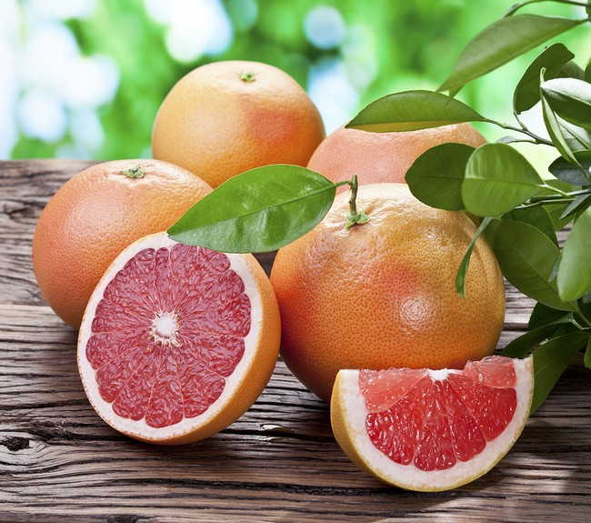 Grapefruits on a wooden table with green foliage