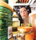 a woman peering into an open fridge
