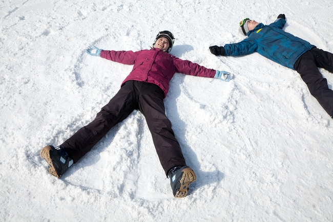 Man and Woman Lying on the Snow Making Snow Angel