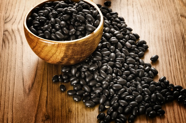 Frijoles, mexican black beans, on wooden background,