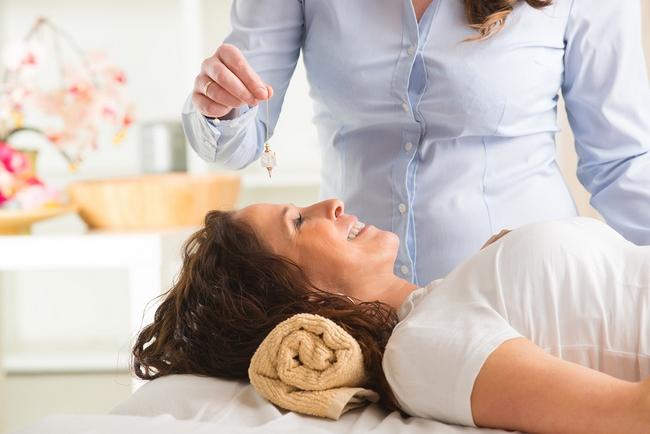 Alternative medicine therapist using pendulum to make a diagnosi