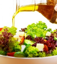 Fresh salad with olive oil isolated on white background, pouring