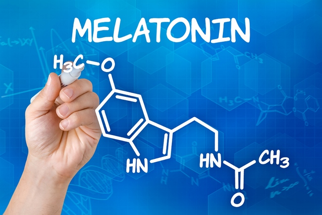 Hand with pen drawing the chemical formula of melatonin