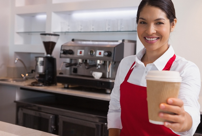 Happy young barista offering cup of coffee to go smiling at came