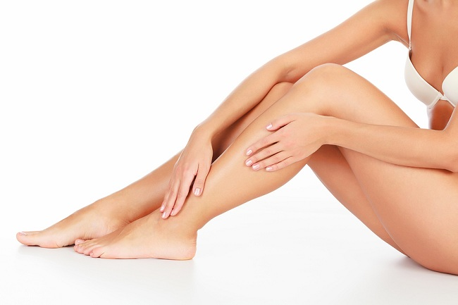 Woman touches her leg, white background, copyspace