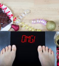 """Digital scales with woman feet on them and sign""""OMG!"""" surrounded by christmas decorations sweets and alcohol. Demonstrates consequences of surfeit and eating unhealthy food during Christmas holidays."""