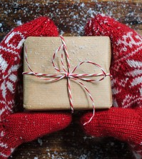 Female hands in winter gloves with christmas gift box
